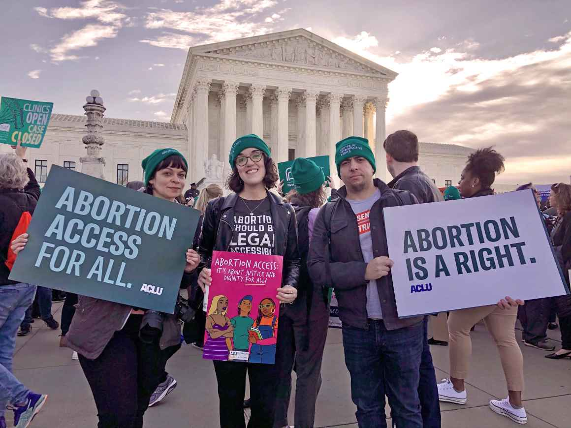 ACLU staff members Nicole McCann on the left and Sergio España on the right hold signs that say Abortion Access for All and Aboriton is a Right. They are in front of the Supreme Court for an abortion rights rally.