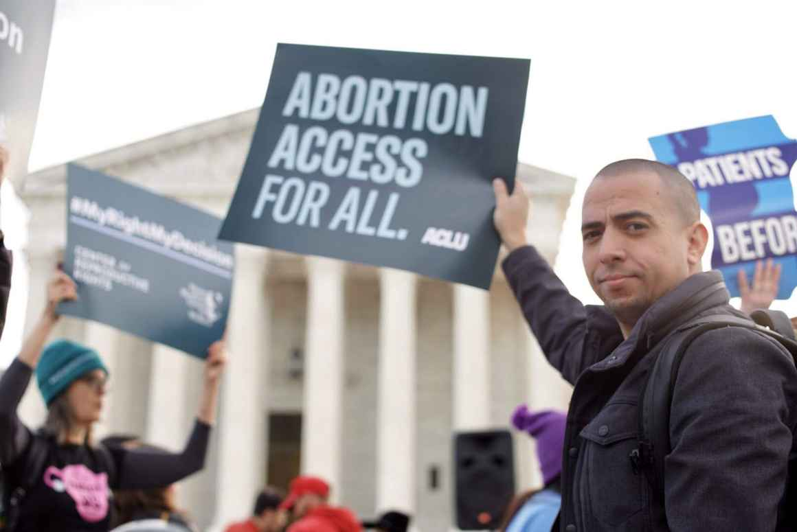 At an abortion rights rally, Sergio España holds an ACLU sign that says Abortion Access for All in front of the Supreme Court of the United States.