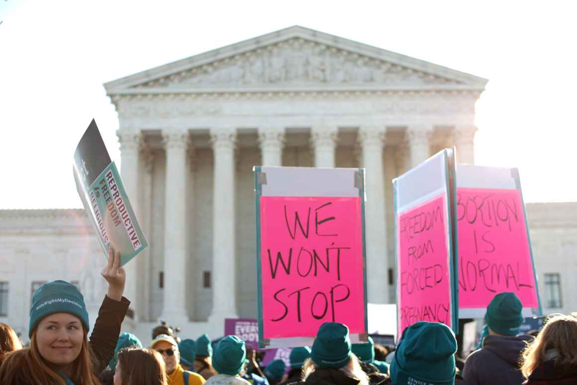 At an abortion rights rally in front of the Supreme Court, people hold signs that say We Won't Stop.