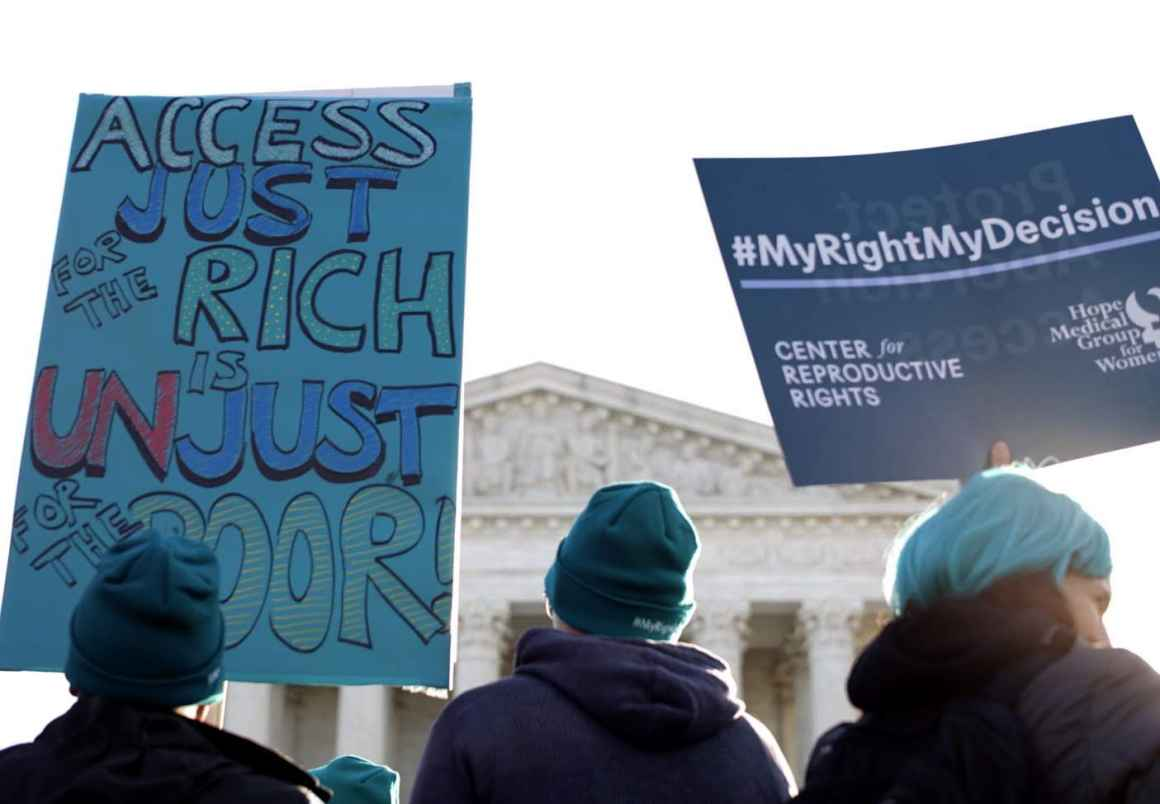 At an abortion rights rally in front of the Supreme Court, protesters hold a sign that says Access Just for the Rich is Unuust for the poor.