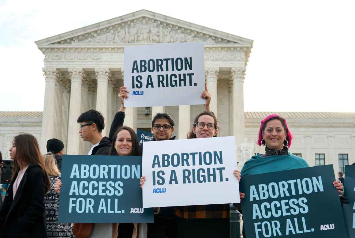 Protesters hold ACLU abortion rights posters in front of the Supreme Court.