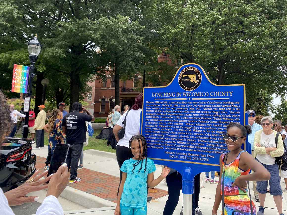 2021 Freedom Riders gather near the Lynching in Wicomico County memorial sign. A person is taking the photo of two Black children standing by the sign.