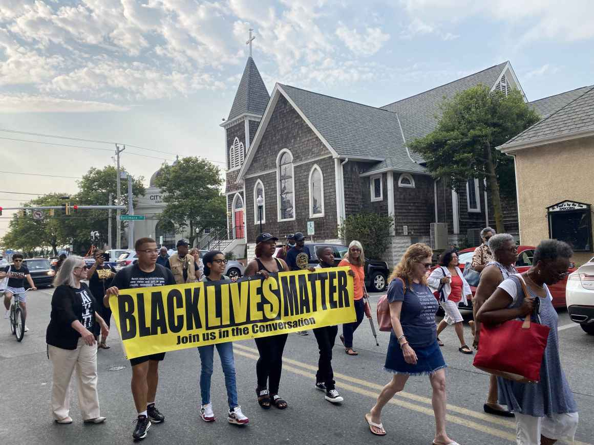 2021 Freedom Riders are marching down the street with a Black Lives Matter sign.