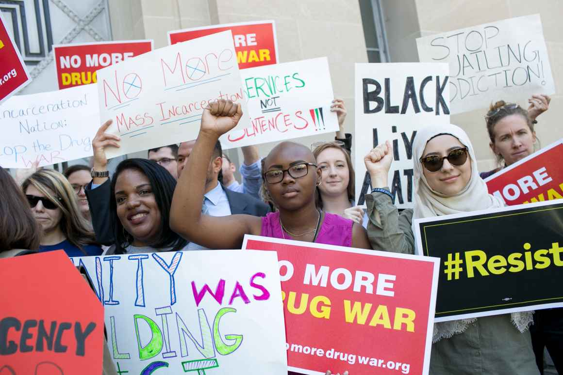 """Protest with a Black person in the center with their fist raised. The signs say """"no more drug war"""" and """"Black Lives Matter"""" and """"resist""""."""