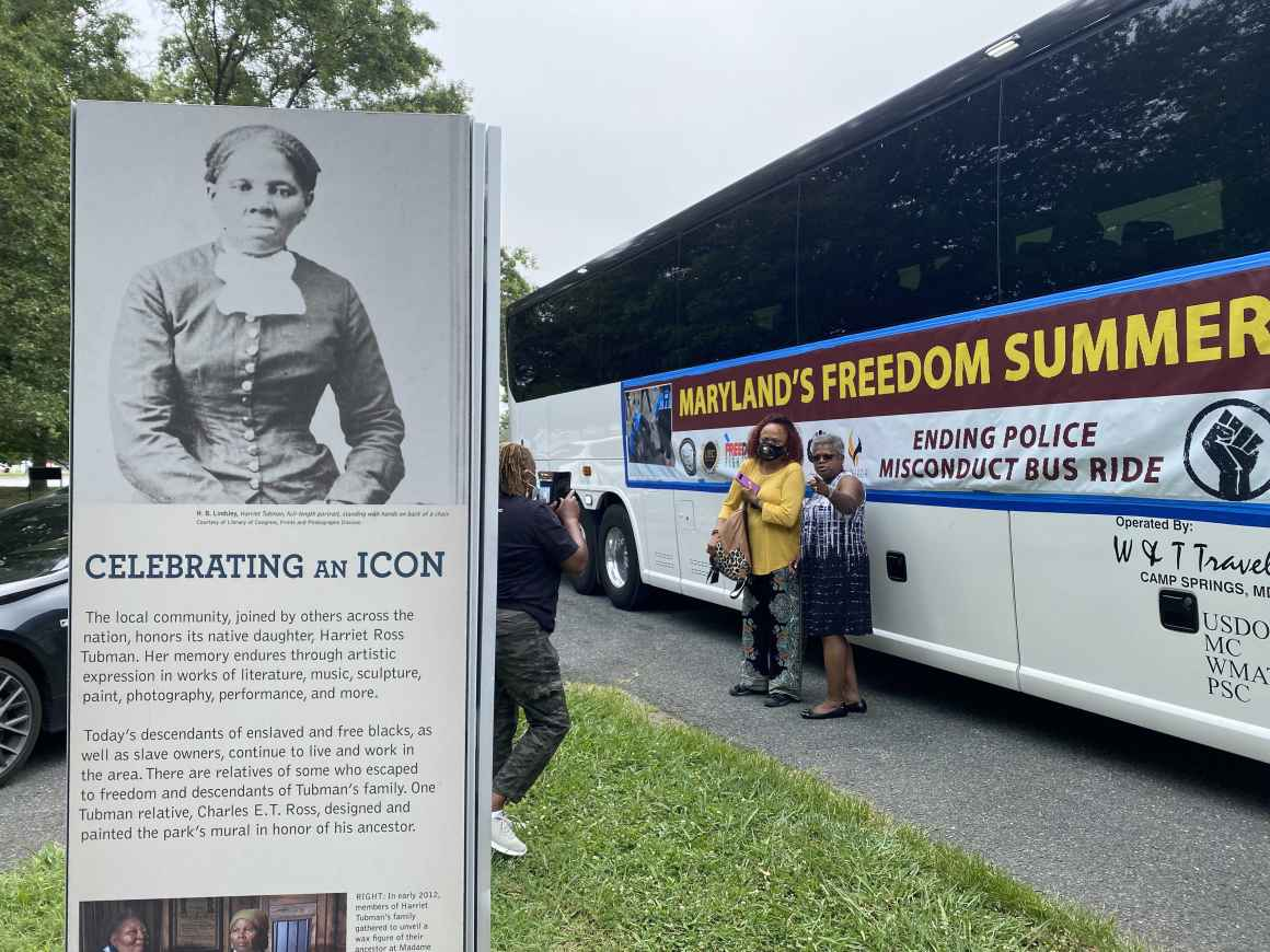 Maryland's Freedom Summer bus beside a sign celebrating the icon Harriet Tubman.