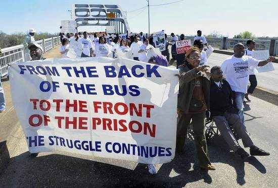 """Black marchers on the Edmund Pettus Bridge holding a banner that says """"From the back of the bus ot the front of the prison, the struggle continues."""""""