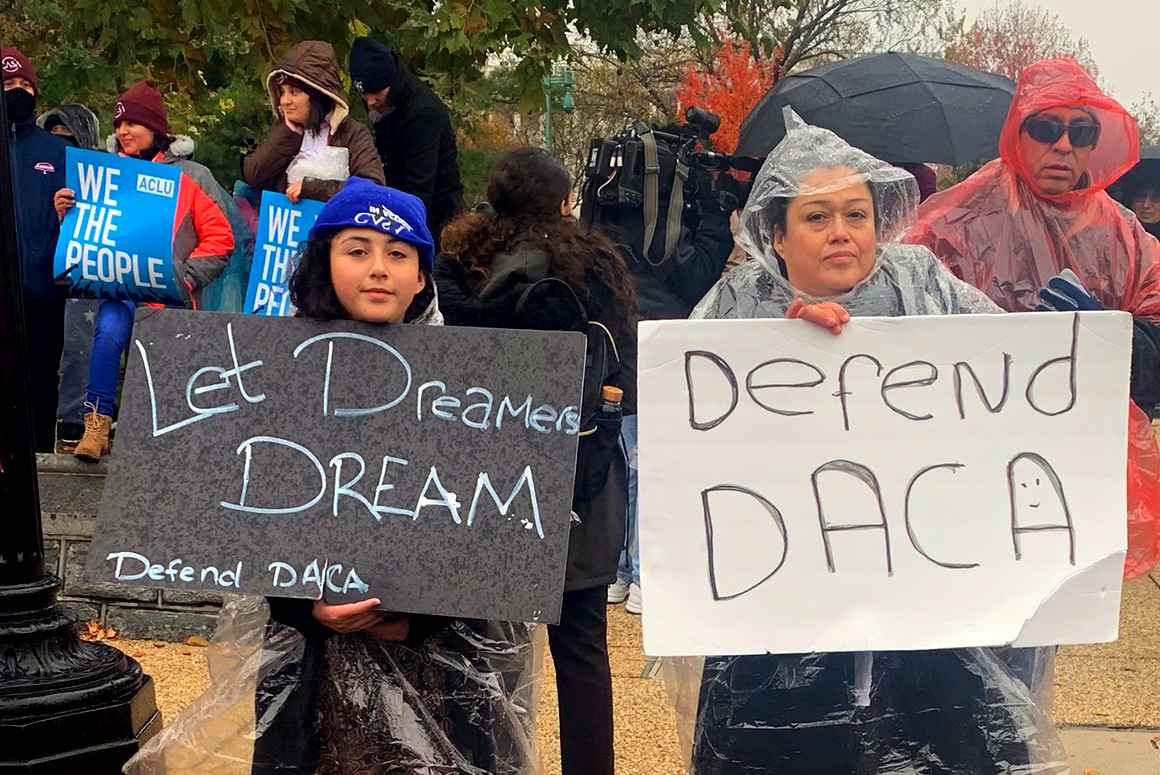 "Two people at the Home is Here rally at the Supreme Court holding signs that say ""Let Dreamers Dream"" and ""Defend DACA"". In the background are two people holding ACLU signs that say ""We the People""."