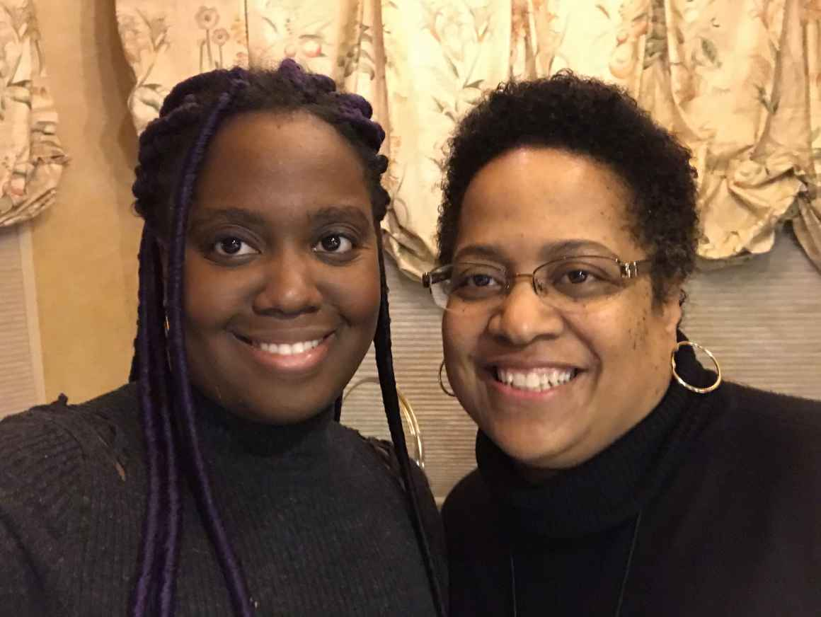 Amber Taylor (left) and her mom (right) take a selfie. They both have natural hair styles. Amber is wearing long faux locs.
