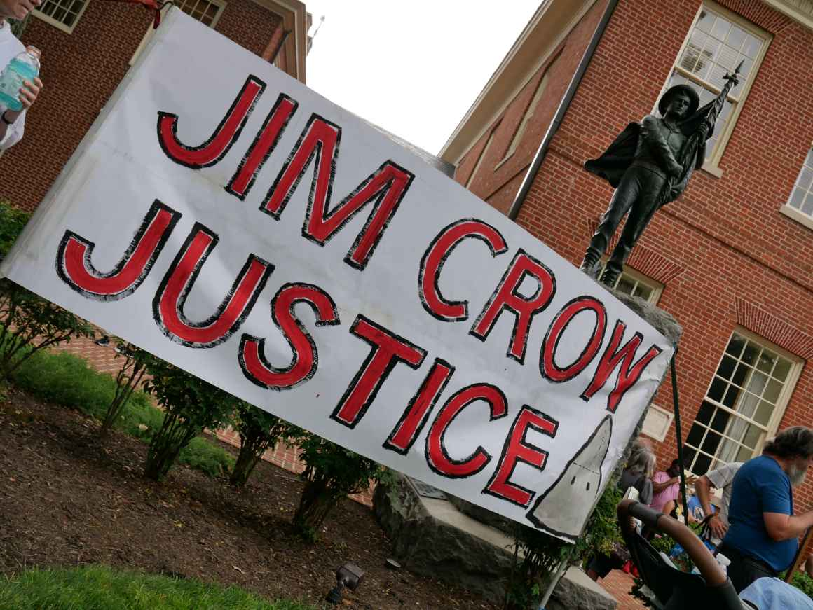 Jim Crow Justice banner is held up in front of the Talbot Boys Confederate statue on the courthouse lawn in Easton, Maryland.