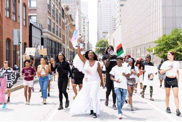 Baltimore Safe Haven photo of 2nd Black Trans Live Matter March in July 2021. Photo shows a line of people marching down a Baltimore Street. The person in the middle is holding up a trans flag.
