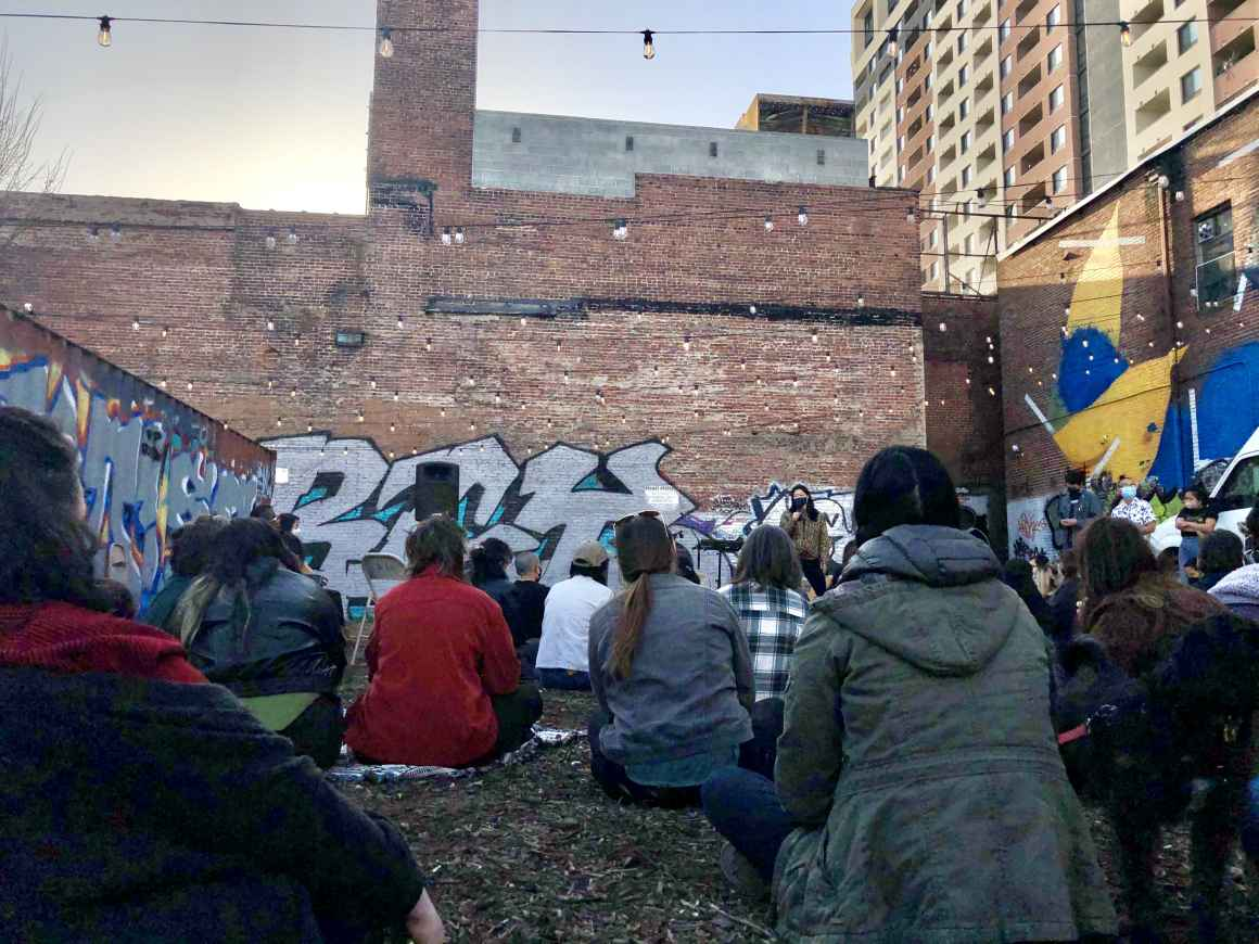 People sit on the ground listening to a speaker at the vigil at the YNot Lot in Baltimore for the victims of the shooting in Atlanta, GA. Asian people in Baltimore spoke about their own experiences.