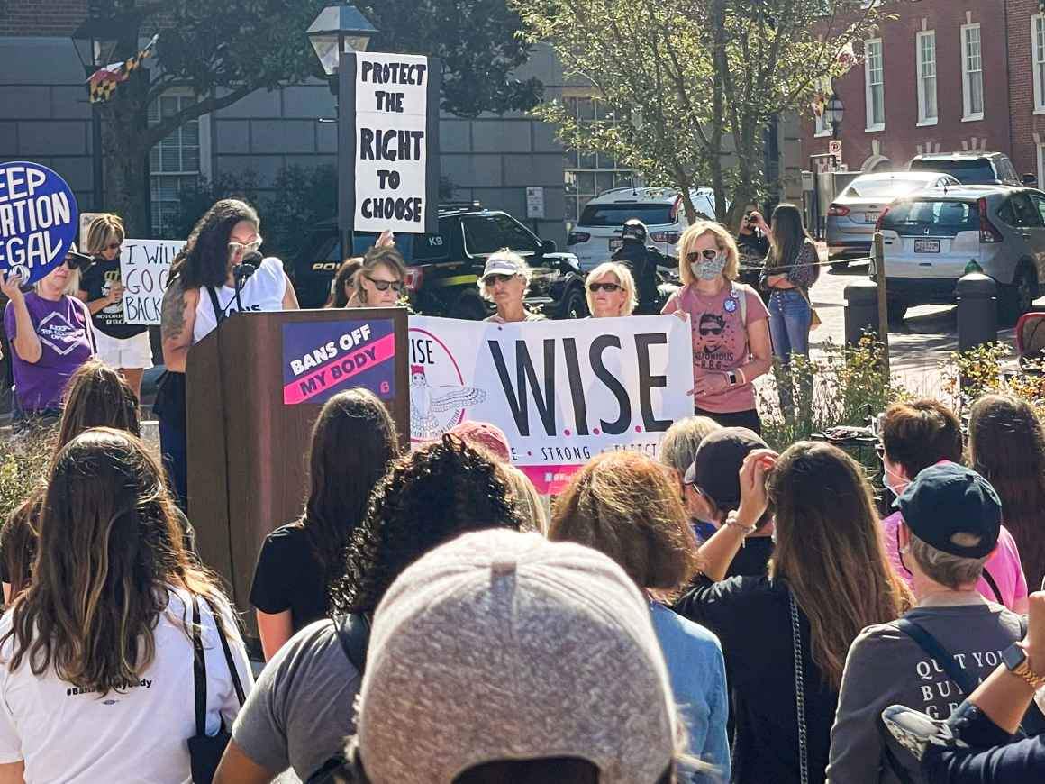 Ashley Esopsito speaks at an abortion access rally in Annapolis, MD. She is a Black woman standing at a podium with people standing in Lawyer's Mall.