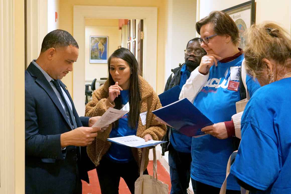 ACLU of Maryland members are talking with Senator Antonio Hayes at the Lobby Day 2020 event in Annapolis wearing blue ACLU t-shirts.