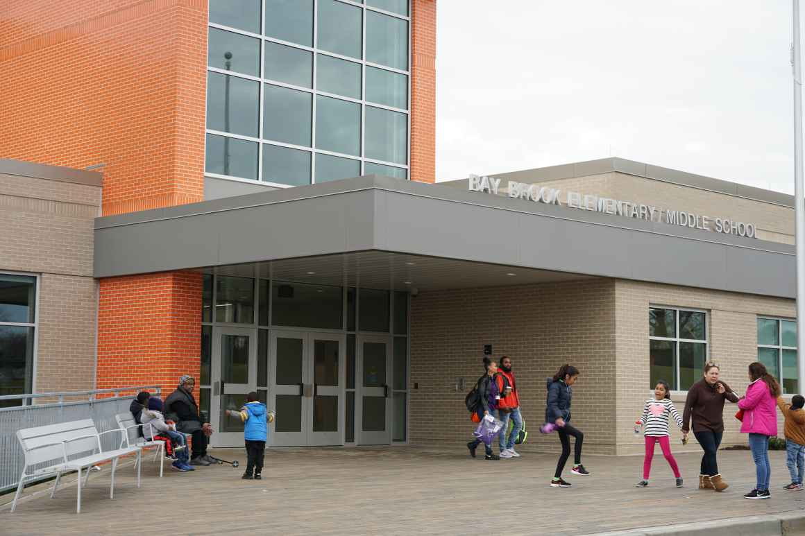 Children, parents, and school staff are standing out front of the brand new Bay-Brook Elementary / Middle School in Baltimore, MD. The are lots of windows and a colorful orange facade.