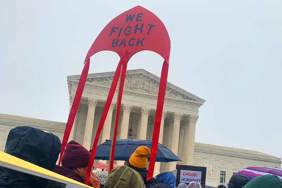 "A large crowd of people are holding protest signs and gathered in the rain in front of the Supreme Court in Washington, DC. One big ride kite sign says ""We fight back!"""