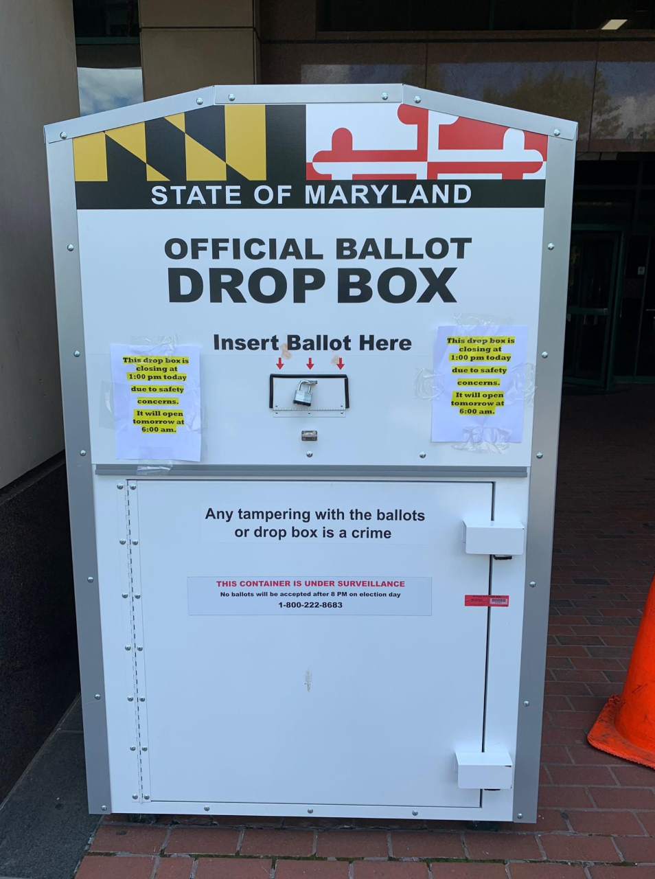 Picture of a Maryland official ballot drop box. It is a white, rectangular shaped box with the State of Maryland name and flag on it and it says Official Ballot Drop Box and insert Ballot Here. There is a small opening in the middle with three red arrows.