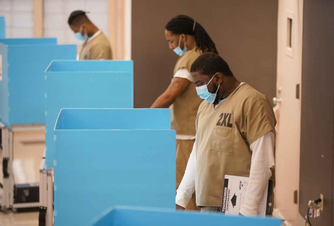 Picture shows a few Black people who are incarcerated wearing surgical masks voting.