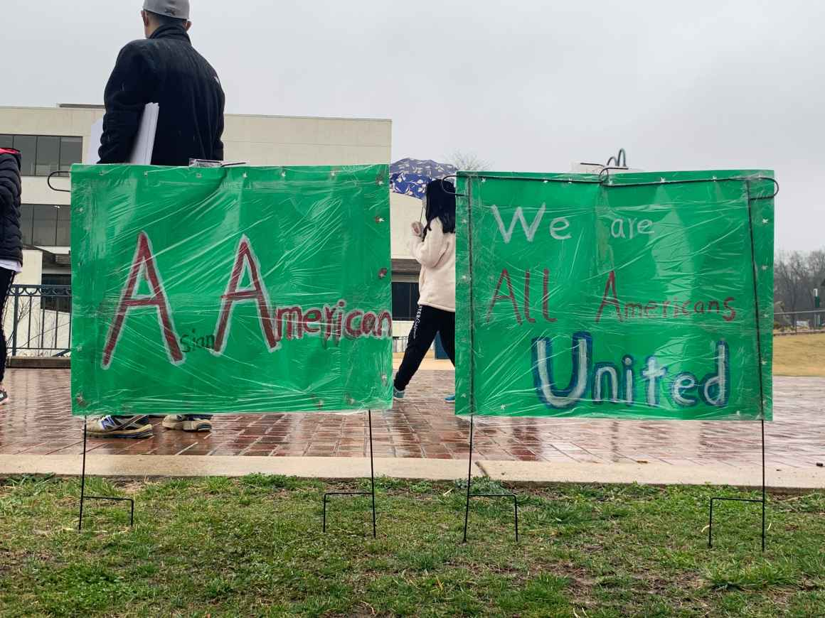 """A person at the Stop Asian Hate rally in Columbia, Maryland, is standing in front of two green signs that say, """"A Americans"""" and """"We are all Americans United."""""""