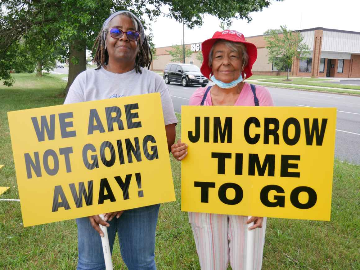 """Two Black elders hold signs that say, """"We are not going away!"""" and """"Jim Crow time to go."""""""