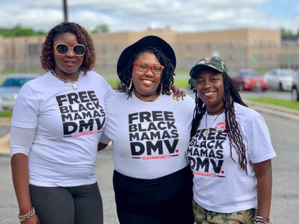 """Qiana Johnson, on the left, is with two other Black people wearing t-shirts that say """"Free Black Mamas DMV""""."""