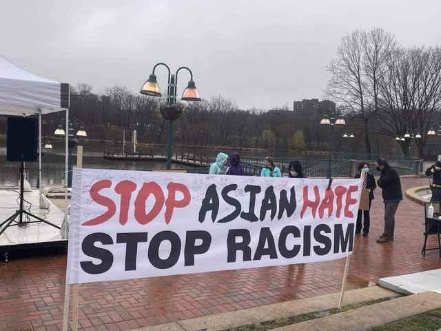 """Stop Aisan Hate - Stop Racism"" banner on a rainy brick sidewalk."