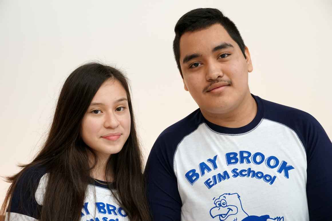 Tarsis Garcia (left) and Brandon Rivera (right) are Latinx students wearing shirts for their school Bay-Brook Elementary/Middle School. Tarsis has long dark brown hair and Brandon has short dark brown hair.