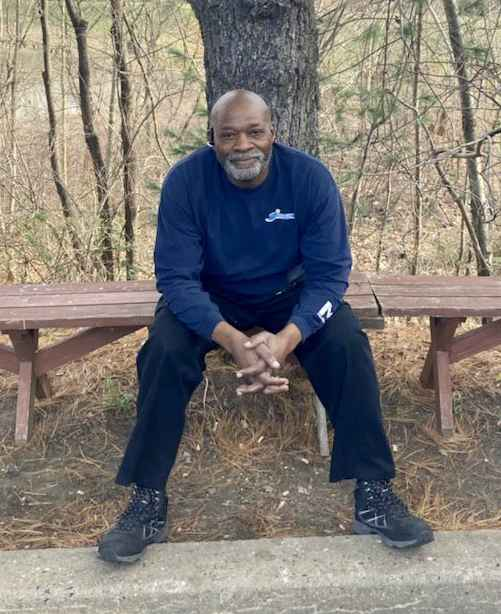 Picture of Calvin McNeill, a Black man with bald head, sitting on a bench in front of a tree.