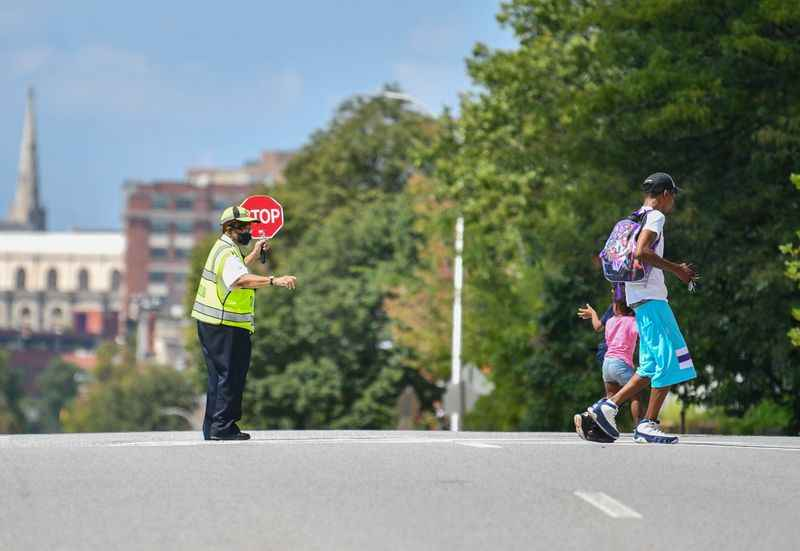 A crossing guard is guiding two students across a street.