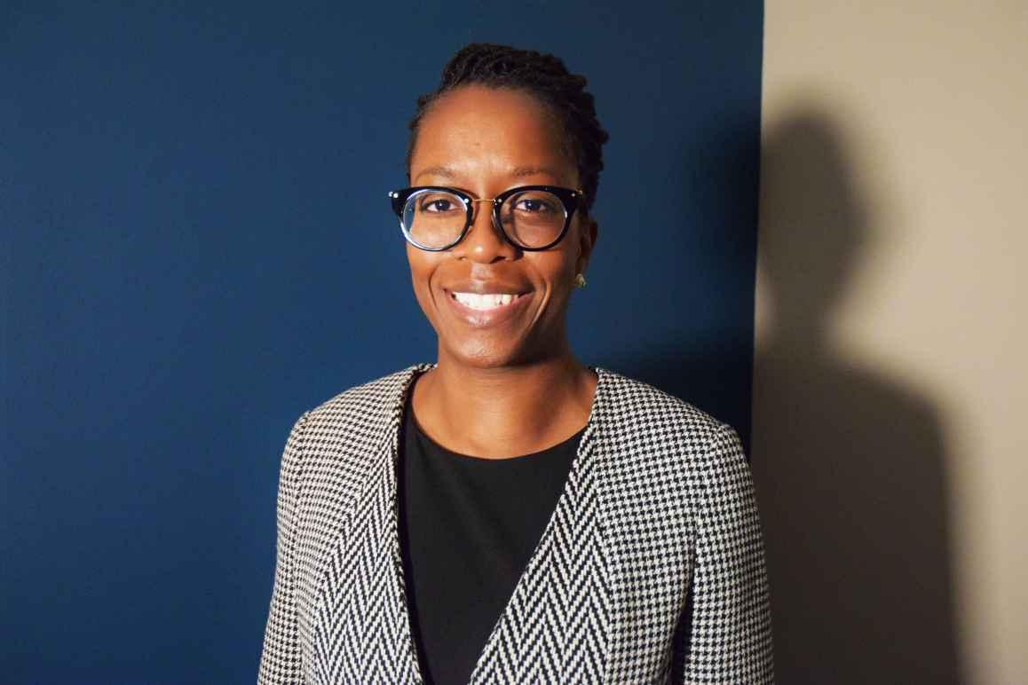 Boatemaa Ntiri, a Black woman, shirt hair, wearing glasses and a herringbone jacket and black shirt