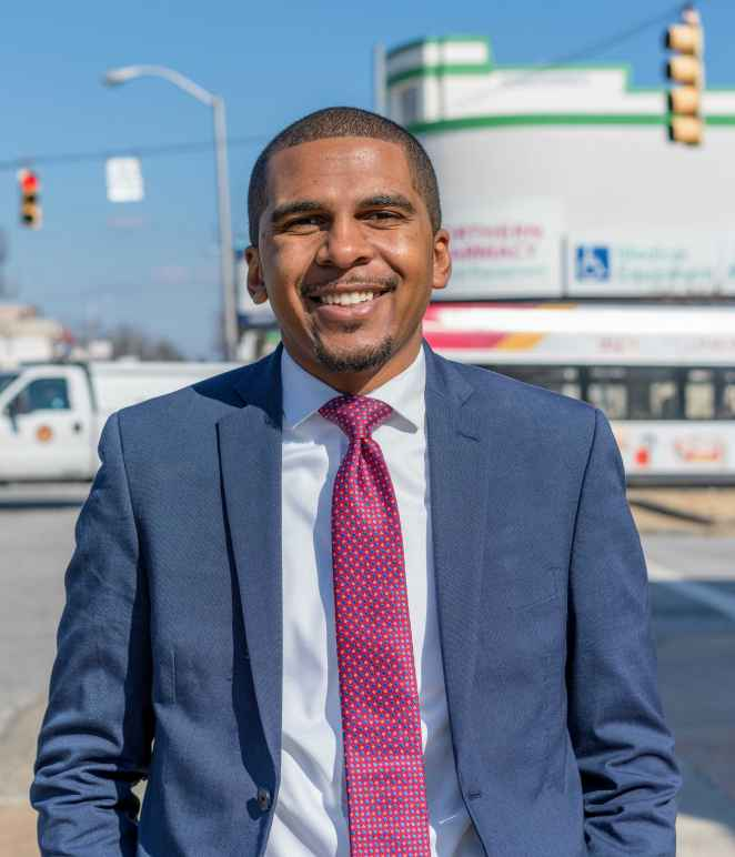 Image shows a picture of Caylin Young in a blue suit and fuschia time. He is standing on a Baltimore City street on a sunny day. He is a Black may with short hair and he is smiling in the photo.