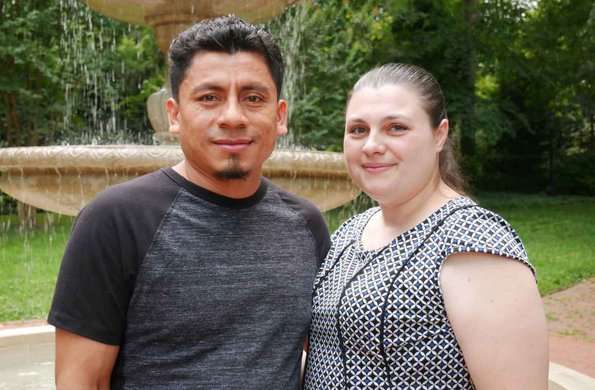 Elmer (left) and Alyse (right) Sanchez are standing in front of a water fountain with green trees behind them.