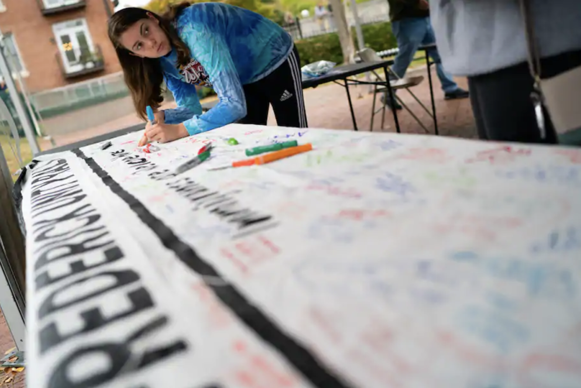 A woman signs a banner at a rally in support of immigrants in Frederick in 2019. (Sarah L. Voisin/The Washington Post)