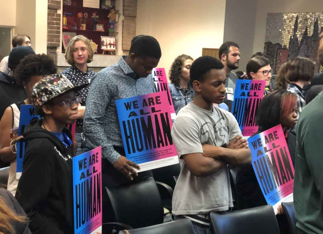 We are all human - students at school board meeting holding posters