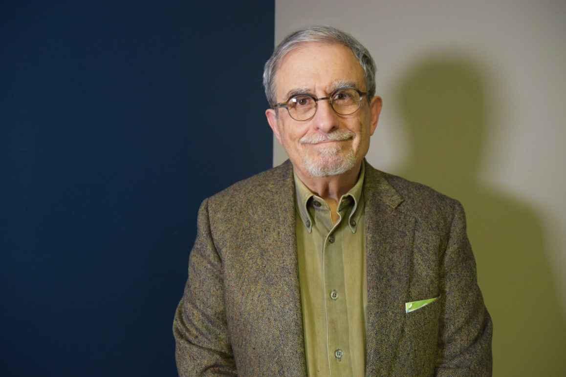 John Sondheim, white man, short gray hair, wearing glasses, a brown suit with greenish brown collared shirt