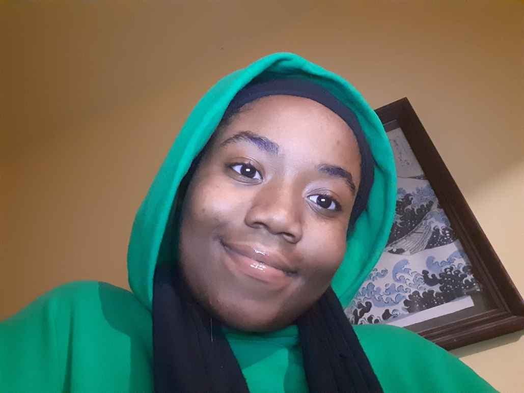 Queen Royalty is wearing a green hoodie with the hood up.