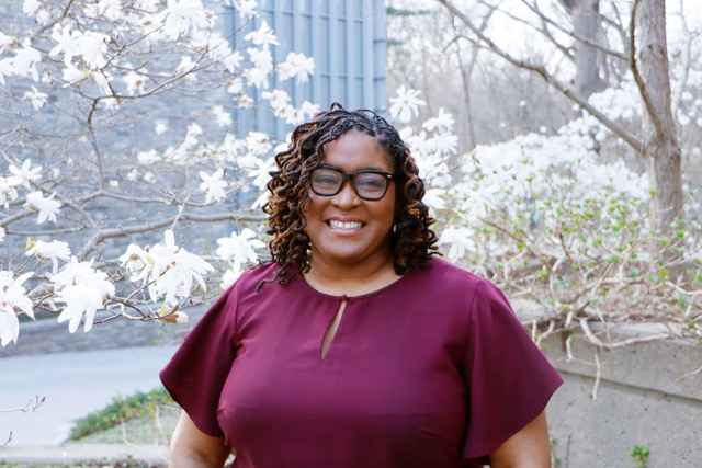 Sheila Graham is a Black-Latina centered in the photo in from of flowering trees.