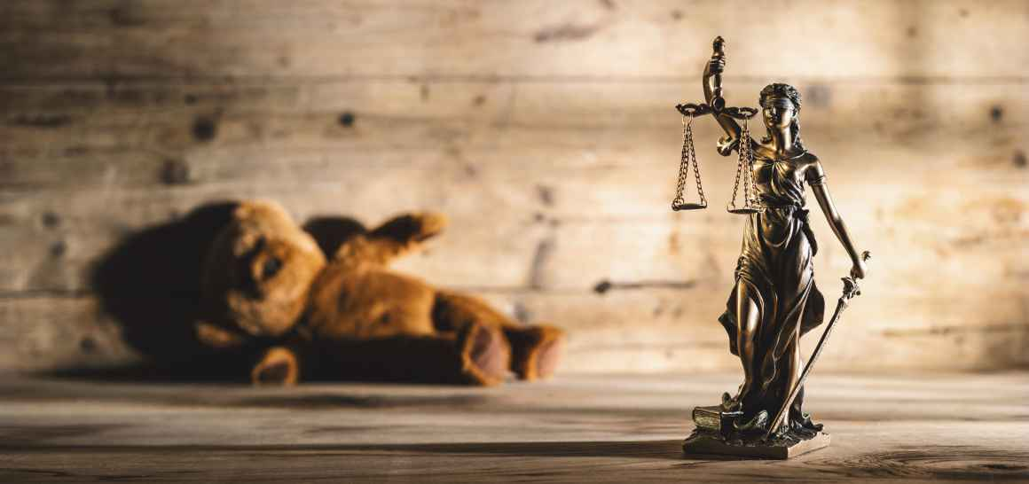 Image shows justice scales and statue and a teddy bear laying on its side.