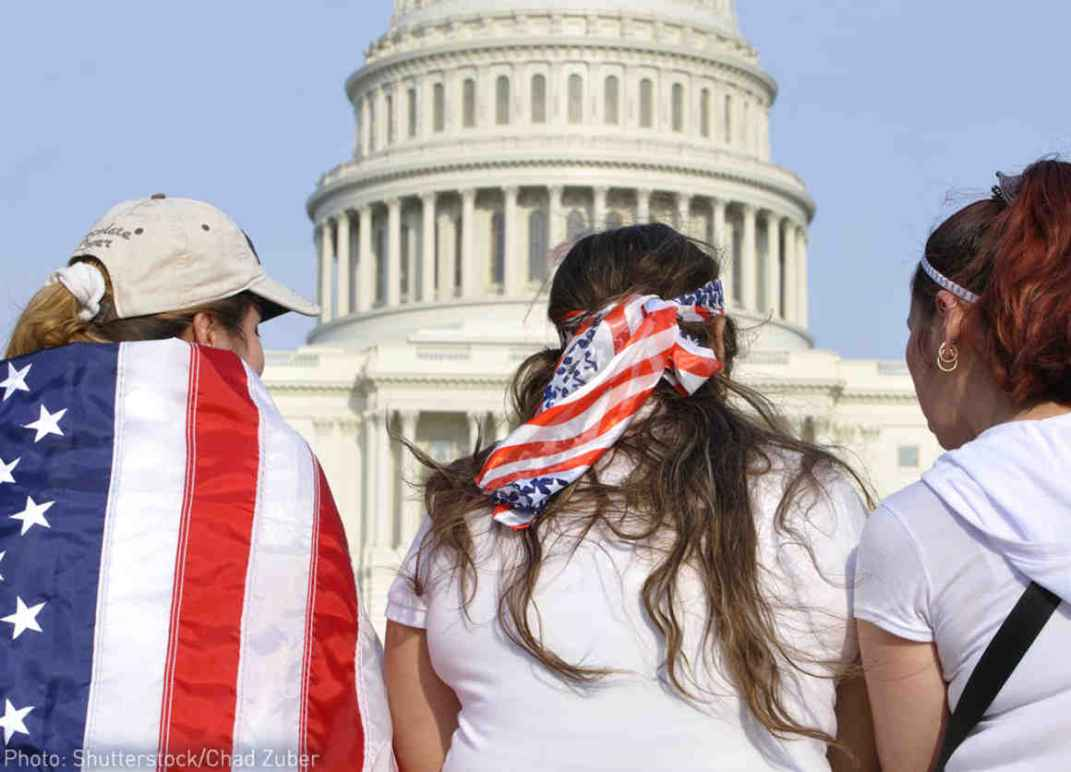 Three people are facing the US Capitol Building with American flags