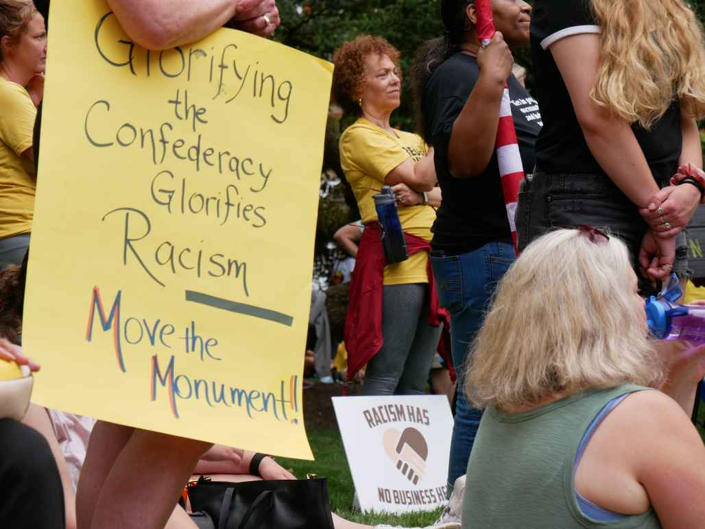"""Person holds a sign that says, """"Glorifying the Confederacy Glorifies Racism. Move the Monument."""" Another sign is visible that says, """"Racism has no business here."""""""
